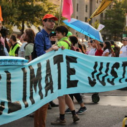people hold climate justice banner
